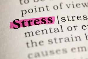 Stress im Büro. Das Wort Stress in in einem Lexikon markiert.